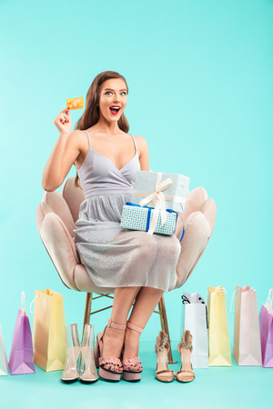Full length portrait of brunette shopper woman sitting on armchair while choosing girlish sandals and buying with credit card isolated over blue background