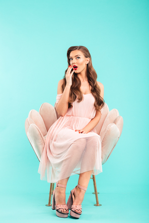 Full length photo of excited woman 20s in pink dress sitting in soft armchair with legs crossed and open mouth isolated over blue background