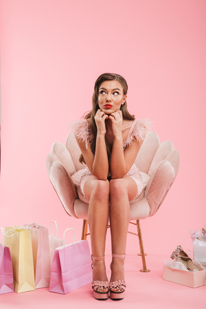 Full length portrait of beautiful dreaming woman in dress propping her head while sitting in armchair with shopping bags and shoes isolated over pink background