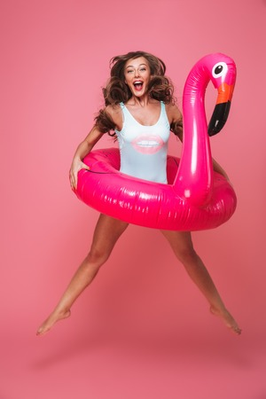 Full length portrait of a joyful young woman dressed in swimsuit jumping with inflatable flamingo isolated over pink background