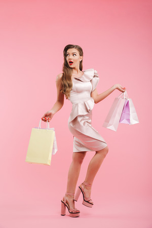 Full length photo of beautiful woman 20s in dress looking back on copyspace and holding colorful shopping bags isolated over pink background