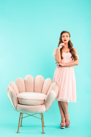 Full length photo of elegant woman 20s in pink dress standing near cozy soft armchair isolated over blue background Stock Photo