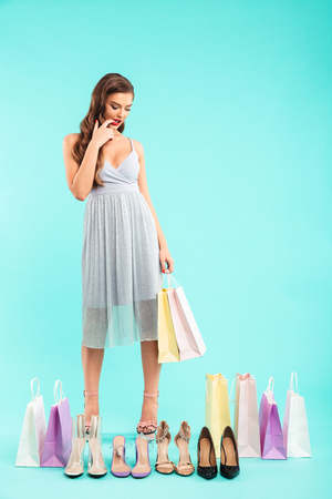 Full length photo of puzzled shopper woman 20s in dress shopping and doubting while posing with lots of shoes isolated over blue background