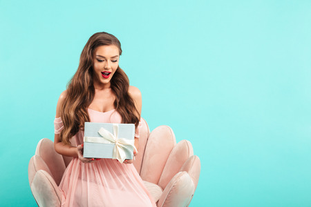 Portrait of beautiful woman 20s in pink dress holding present box while sitting on armchair isolated over blue background