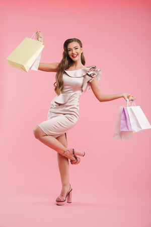 Full length photo of pleased shopper woman 20s in dress smiling and holding shopping bags isolated over pink background
