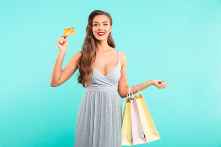 Attractive woman 20s in dress holding shopping packages and showing golden credit card isolated over blue background
