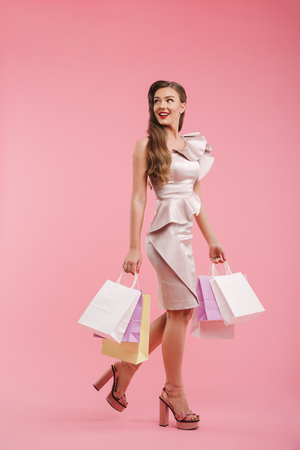 Full length photo of smiling woman 20s in dress looking back on copyspace and holding colorful shopping packages isolated over pink background