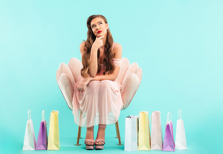 Photo of dreaming woman 20s in dress sitting on pink armchair and thinking after shopping with lots of colorful bags isolated over blue background