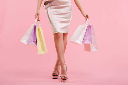Cropped photo of caucasian woman in dress and summer shoes holding colorful shopping bags isolated over pink background