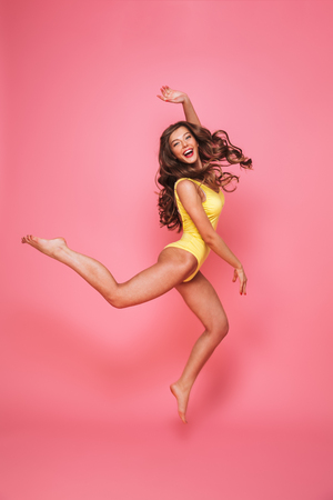 Full length portrait of a cheerful young woman dressed in swimsuit posing while jumping isolated over pink background
