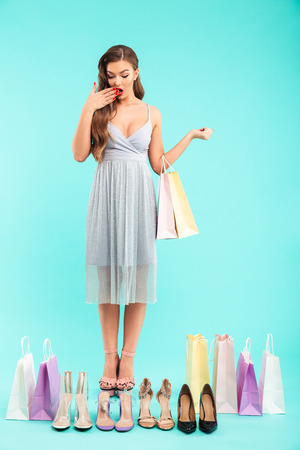 Full length photo of young shopaholic woman 20s in dress shopping and doubting while looking at lots of shoes isolated over blue background