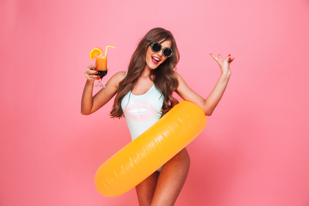 Portrait of an excited young woman dressed in swimsuit posing with inflatable ring and holding a cocktail isolated over pink background