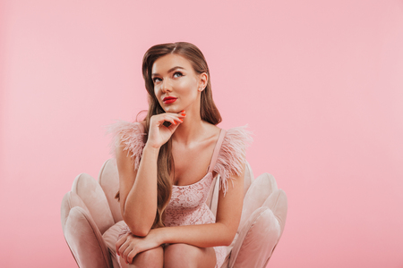 Portrait of stylish thinking woman in dress touching her chin while sitting in armchair isolated over pink background