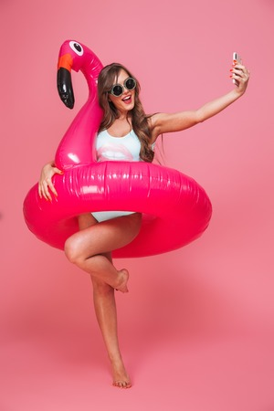 Full length portrait of a cheerful young woman dressed in swimsuit posing with inflatable flamingo while taking a selfie isolated over pink background