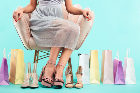 Cropped image of young shopper woman 20s sitting on armchair with lots of sandals and shopping packages isolated over blue background Banco de Imagens