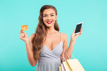 Pleased shopaholic woman posing shopping bags and holding smartphone and credit card isolated over blue background