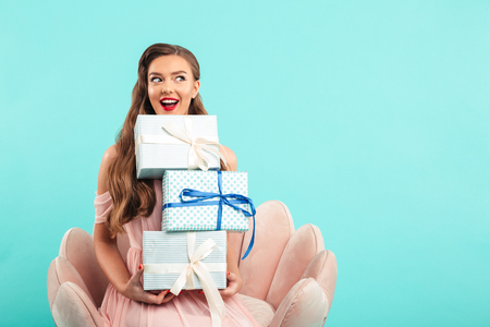 Portrait of beautiful woman 20s in pink dress holding lots of present boxes while sitting on armchair isolated over blue background