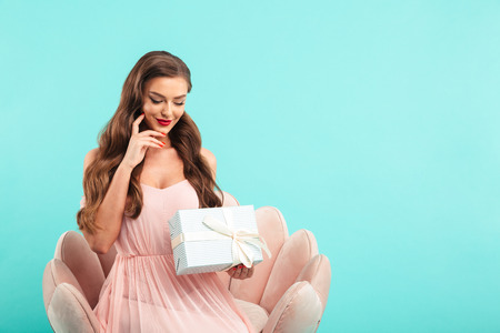 Portrait of beautiful lady 20s in pink dress holding present wrapped box while sitting on armchair isolated over blue background