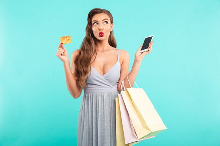 Charming shopaholic woman holding shopping bags and paying with smartphone and credit card isolated over blue background Banco de Imagens