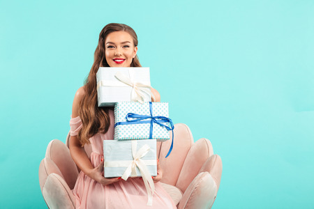 Portrait of gorgeous woman 20s with long brown hair holding lots of gift boxes while sitting on pink armchair isolated over blue background