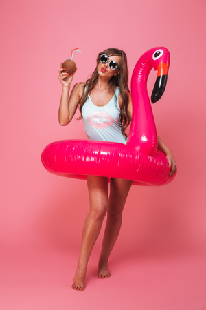 Full length portrait of a lovely young woman dressed in swimsuit posing with inflatable flamingo and coconut cocktail isolated over pink background