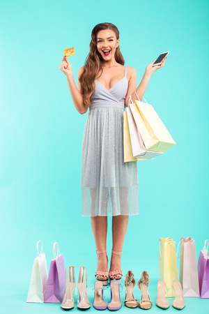 Full length photo of smiling shopaholic woman holding shopping bags and buying summer shoes with smartphone and credit card isolated over blue background