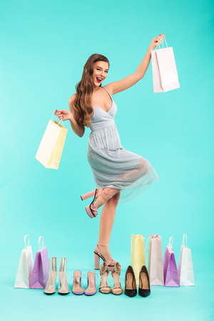 Full length photo of happy shopper woman 20s in dress smiling and holding shopping bags with shoes isolated over blue background Banco de Imagens