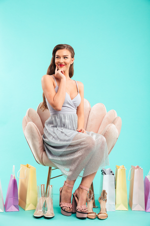 Full length portrait of adorable woman 20s sitting on armchair while shopping and choosing girlish sandals isolated over blue background Banco de Imagens