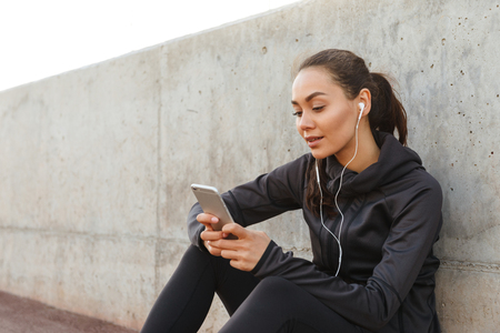 Photo of beautiful young asian sports woman sitting outdoors listening music using mobile phone.