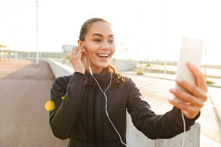 Image of happy young asian sports woman walking outdoors talking by mobile phone.