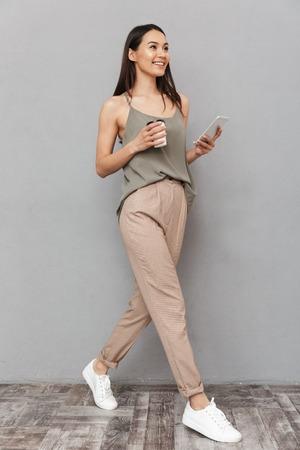 Pełnej długości portret całkiem azjatyckiej kobiety trzymającej filiżankę kawy na wynos i przy użyciu telefonu komórkowego podczas spaceru na białym tle na szarym tle