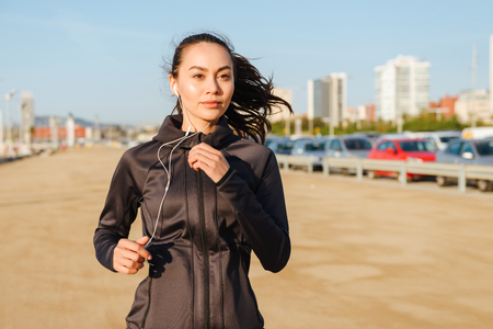 Photo of amazing beautiful young asian sports woman running outdoors listening music.
