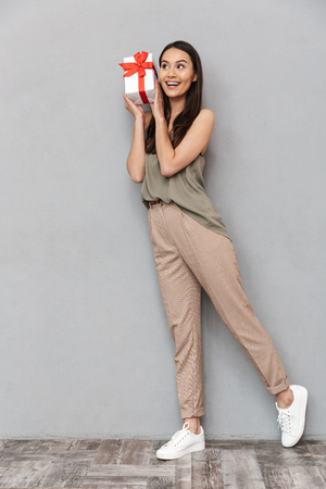 Full length portrait of a pretty young asian woman holding present box over gray background