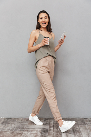 Full length portrait of a smiling asian woman holding takeaway coffee cup and using mobile phone while walking isolated over gray background Foto de archivo