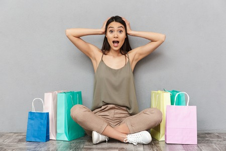 Full length portrait of a shocked young asian woman sitting on a floor with shopping bags over gray background