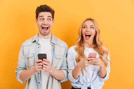 Photo of cheerful man and woman looking at each other with happy emotions while using smartphones isolated over yellow background
