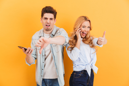 Image of disappointed man using smartphone and showing thumb down while happy woman gesturing finger up after mobile call isolated over yellow background