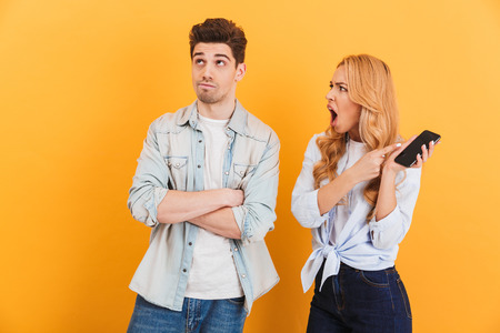 Photo of furious mad woman holding black smartphone and screaming at confused man isolated over yellow background