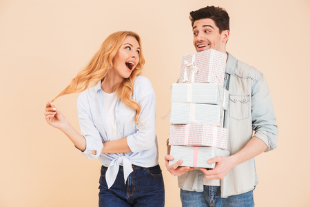 Image of charming woman rejoicing and expressing surprise while handsome man holding lots of gift boxes isolated over beige background