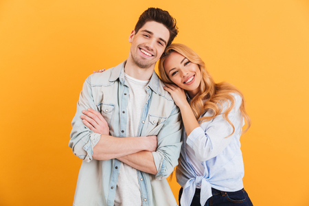 Portrait of content couple in basic clothing smiling at camera while woman putting her head on male shoulder isolated over yellow background