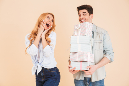 Portrait of handsome brunette man standing with many gift boxes while woman screaming in surprise isolated over beige background Stock Photo