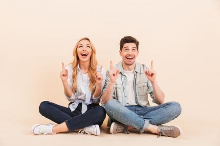 Photo of excited friends man and woman 20s in denim clothing sitting on the floor with legs crossed and pointing fingers upward at copyspace isolated over beige background