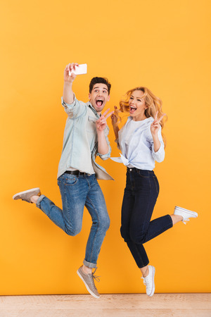 Full length photo of happy man and woman taking selfie photo on mobile phone while jumping and showing victory sign isolated over yellow background Stockfoto