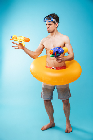 Full length portrait of an excited young shirtless man in swim goggles and inflatable ring having fun with water guns over blue background