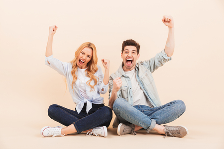 Image of happy two friends man and woman screaming and rejoicing with happy emotions while sitting on the floor with legs crossed isolated over beige background