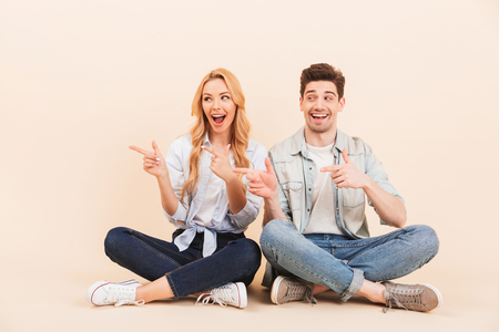 Photo of content two friends man and woman sitting on the floor with legs crossed and pointing fingers aside at copyspace isolated over beige background