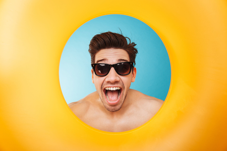 Close up of an excited man in sunglasses looking through inflatable ring at camera over blue background