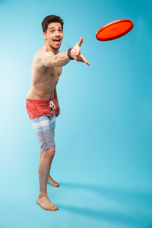 Full length portrait if an excited shirtless man in swimming shorts playing with frisbee over blue background