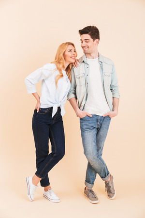 Full length image of positive caucasian couple man and woman in denim clothing smiling and looking at each other isolated over beige background Stock Photo