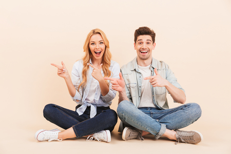 Image of caucasian two friends man and woman sitting on the floor with legs crossed and pointing fingers aside at copyspace isolated over beige background Stock Photo